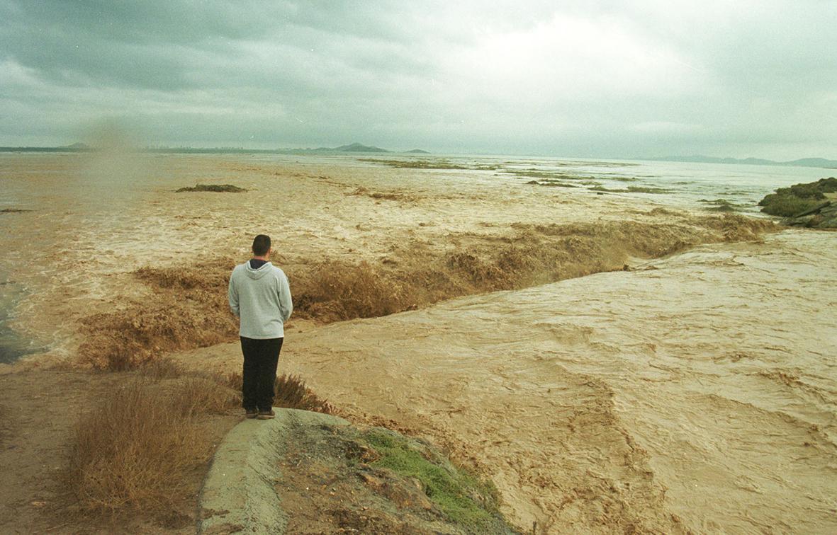 Los Alcázares (Murcia), 23.10.2000.- Un hombre observa la desembocadura de la rambla del Albujón en el Mar Menor, que aporta miles de hectómetros cúbicos de agua dulce y barro procedentes del Campo de Cartagena, durante las inundaciones producidas por las intensas lluvias. Pablo Sánchez del Valle.