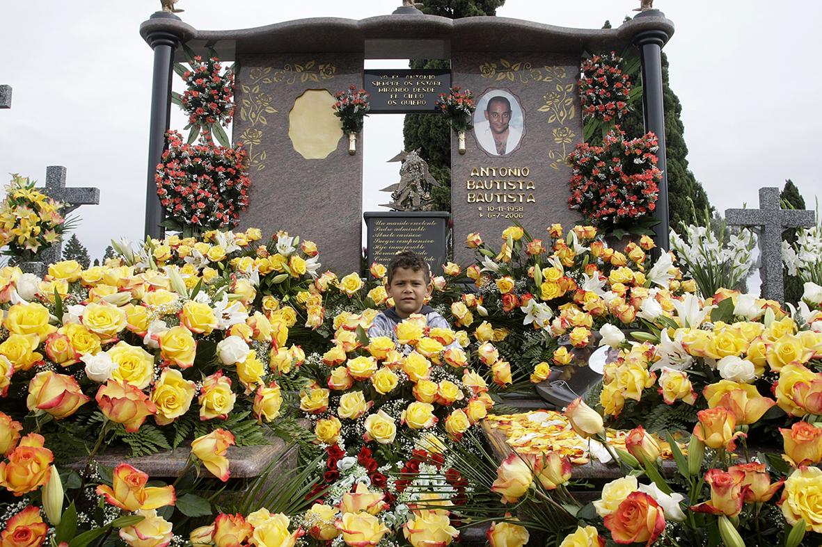 Murcia, 01.11.2008.-  Un niño posa en la tamba de su padre, rodeado por las flores que ha llevado la familia con motivo del día de todos los santos, en el cementerio de Murcia.  Pilar Morales.
