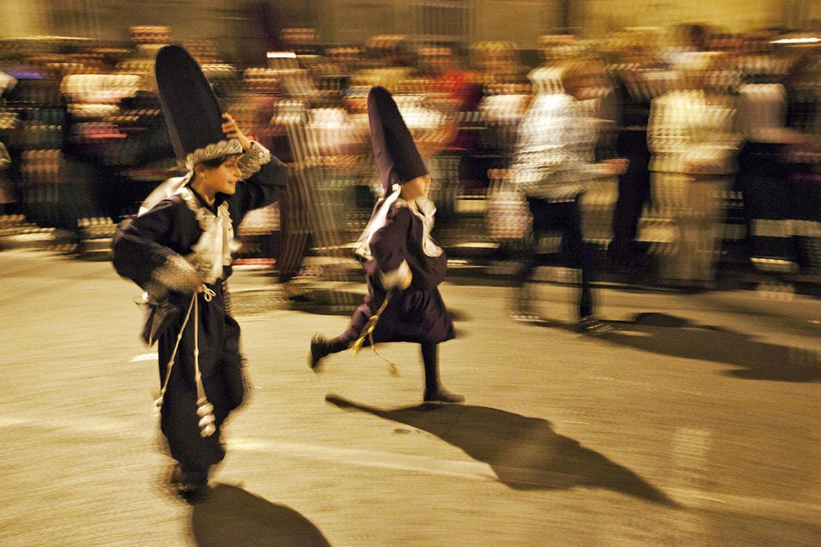 Murcia, 17.04.2014..- Dos niños vestidos de nazarenos corren hacia la zona de salida de la procesión de jueves santo, en la pedanía murciana de Algezares. Gloria Nicolás.