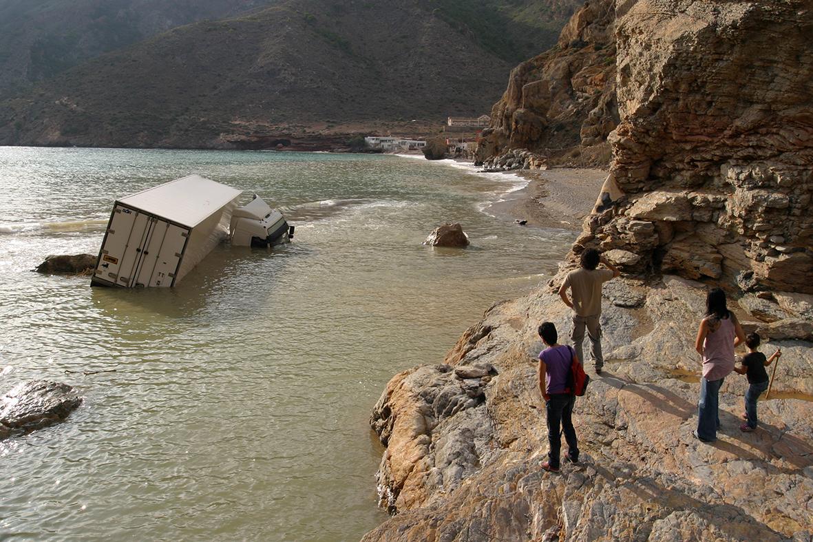 Cartagena (Murcia), 29.09.2009.- Varias personas observan un camión de gran tonelaje que ha sido arrastrado hasta el mar por las inundaciones causadas por las intensas lluvias, junto a la playa de El Portús. Pablo Sánchez del Valle.