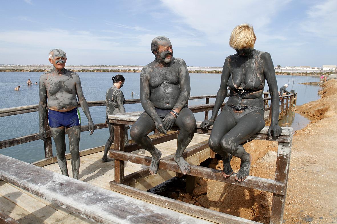 Lo Pagán (Murcia), 11.09.2015.- Unos turistas procedentes de Checoslovaquia se dan baños de lodo junto a las salinas del Mar Menor. Pabolo Sánchez del Valle.