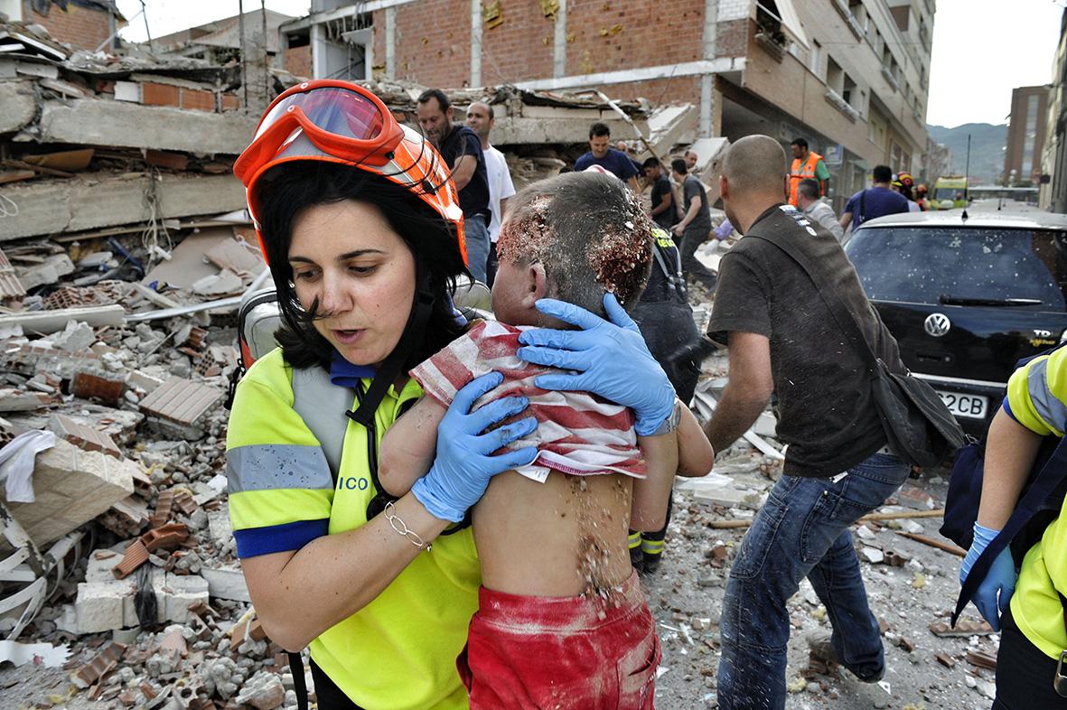 Lorca (Murcia), 11.05.2011.- Una agente de Protección Civil sostiene en sus brazos a un niño rescatado con vida de uno de los edificios que colapsaron durante el terremoto ocurrido en Lorca. Nacho García.