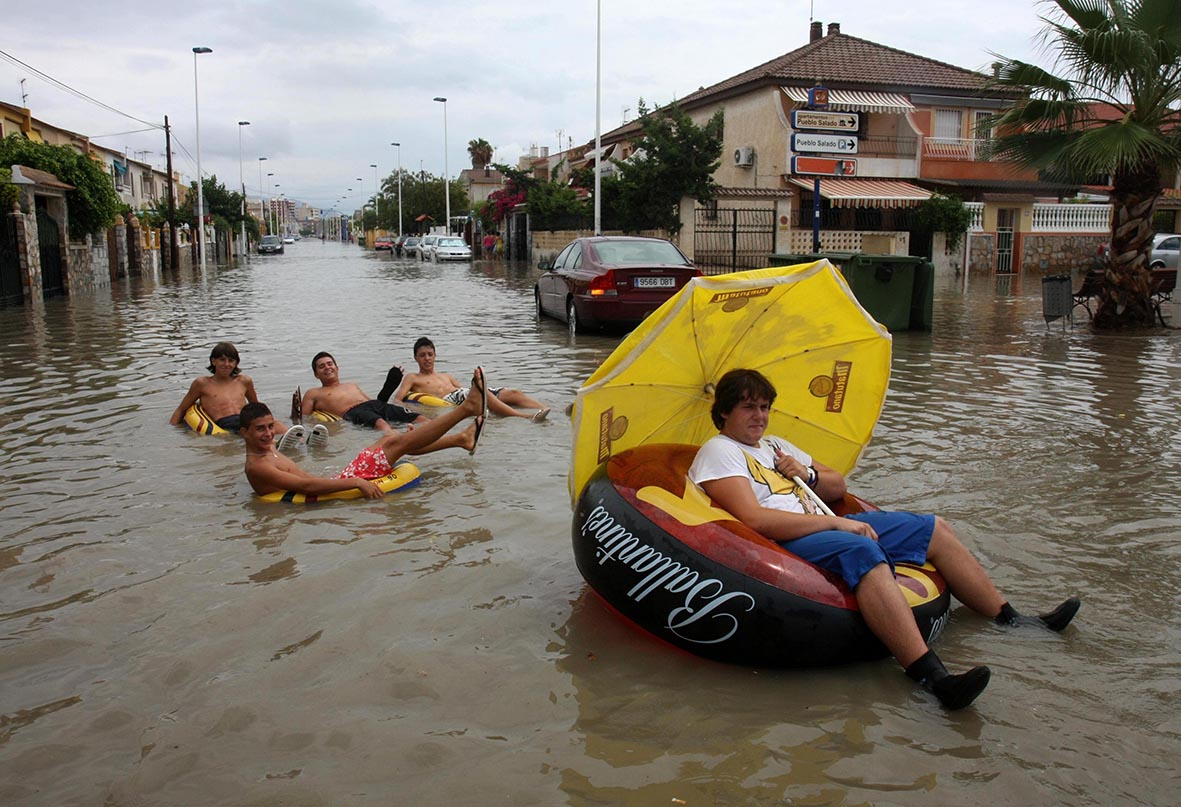 Mazarrón (Murcia), 17.08.2010.- Varios jóvenes se divierten sobre flotadores en una calle inundada de la urbanización Bahía, que sufrió como otros parajes de la zona graves inundaciones a causa de las intensas lluvias. Pablo Sánchez del Valle.