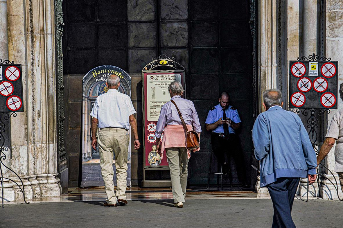Padua (Italia), 03.09.2014.- Un agente de seguridad está distraido consultando su teléfono móvil a la entrada de la Basílica de San Antonio, mientras varios turistas consultan los carteles anunciadores. Carlos Trenor.